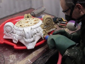 Heavy paint buildup on this carved wooden column capital is softened by steam and removed with careful scraping.