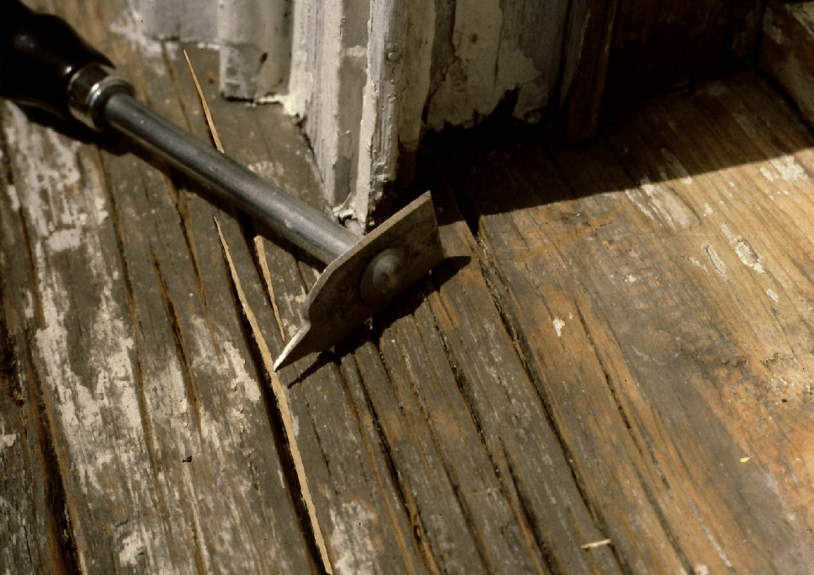 A wooden window sill has deep cracks. A tool lays on the sill.